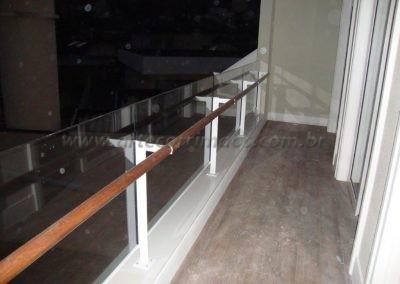 Guarda corpo vidro incolor e corrimão de madeira sacada