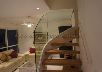 detalhe escada curva com guarda corpo de vidro curvo