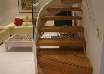 escada na sala com curva e guarda corpo de vidro curvo